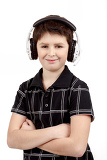 portrait of a happy smiling young boy listening to music on headphones against white background