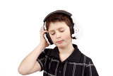 Fotografie portrait of a happy young boy listening to music on headphones against white background