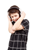 Fotografie portrait of a happy smiling young boy listening to music on headphones against white background