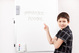 Fotografia little boy with white board showing paragraphs in word impossible