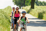 Fotografie mother with two sons riding bike on bicycle trip focus to mother
