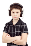 portrait of young boy listening to music on headphones against white background