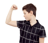 portrait of a young boy with hand raised up and showing its own muscles against white background