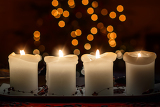 Fotografia burning candle and christmas decorations on wooden table on dark background with bokeh from christmas tree