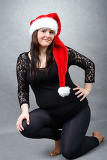 beautiful smiling pregnant young santa woman tenderly holding her tummy