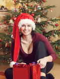 beautiful middle age woman in red party santa hat sitting near the christmas tree with gifts