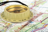 Fotografie old touristic handheld compass on detailed territory map