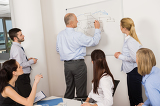 Colleagues Discussing Strategy On Whiteboard