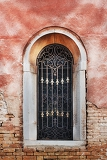 Photo old window with decorative bars on red facade