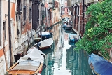 narrow canal among old colorful brick houses in venice italy