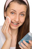 Fotografie Girl with braces using makeup removal