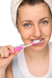 Fotografie Girl with braces brushing teeth isolated