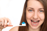 Girl with braces holding toothbrush isolated