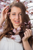 Fotografie Girl with braces holding blossoming tree branch
