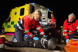 Photo Paramedical team assisting injured motorbike driver