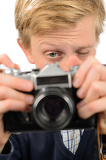 Teenage boy photographing through retro camera