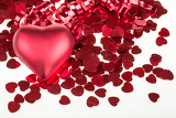Fotografie small red confetti and big hearts on white background