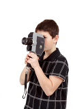 young boy with old vintage analog 8mm camera looking to viewfinder
