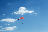 silhouette of unidentified one skydiver on blue sky