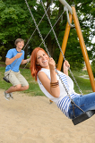 Fotografie Laughing teenage couple on swing in park