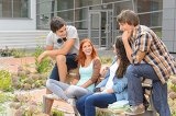 Student friends sitting outside campus laughing
