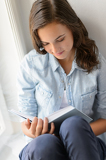 Teenage girl reading book sitting by window