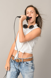 Fotografie Singing teenage girl with microphone closed eyes