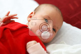 newborn lying one month old baby in red dress with pacifier