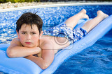 Fényképek happy young boy with inflatable water lounger in the swimming pool