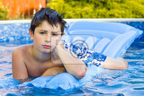 happy young boy with inflatable water lounger in the swimming pool