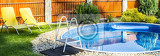 panorama of small home swimming pool with yellows sun loungers
