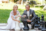Photo beautiful young wedding couple blonde bride and her groom with outdoor ches bride holding white chess checkers and groom black king