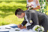groom signing wedding certificate in park with bride in background