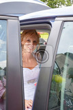 attractive caucasian bride sitting in car and smile to the camera