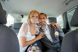 Fotografia beautiful young wedding couple blonde bride with flower and her groom in car wide shoot