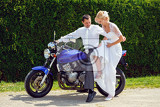 beautiful young wedding couple blonde bride with flower try sit to motorcycle with her groom