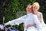 beautiful young wedding couple blonde bride with flower on motorcycle with her groom