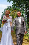 Fotografie happy just married couple under a rice rain outdoor in sunny day