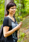 woman smiling and sightseeing outdoors and holding a map in forrest