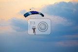 silhouette of unidentified skydiver parachutist on blue sky on sunset