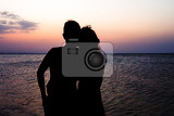 Fotografie couple man and woman holding hands in love staying on beach seaside with sunset scenery people romantic relationship and friendship concept