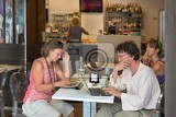 cortona italy  july 1 people after lunch sitting in a cafe and relax while working on laptop july 1 2014