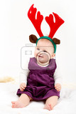 child girl with reindeer antlers on white background