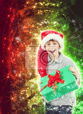 Fotografie surprised boy in santa hat with christmas present on abstract christmas background