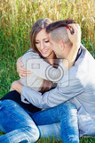portrait of happy smiling young couple in love embracing outdoor at sunny day