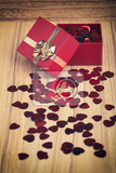 Fotografie small red hearts confetti and present box on wooden background in retro color tone