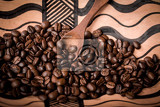 Fotografie pile of fresh and bio aromatic coffee beans in african bowl and wooden spoon