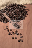 pile of fresh and bio aromatic coffee beans and wooden spoon with space for text
