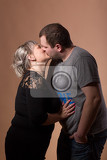 studio shoot of beautiful fashion xxl woman kissing her husband happy couple love concept