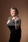 Photo portrait of beautiful smiling plus size young blond woman posing with designer handbags and black dress